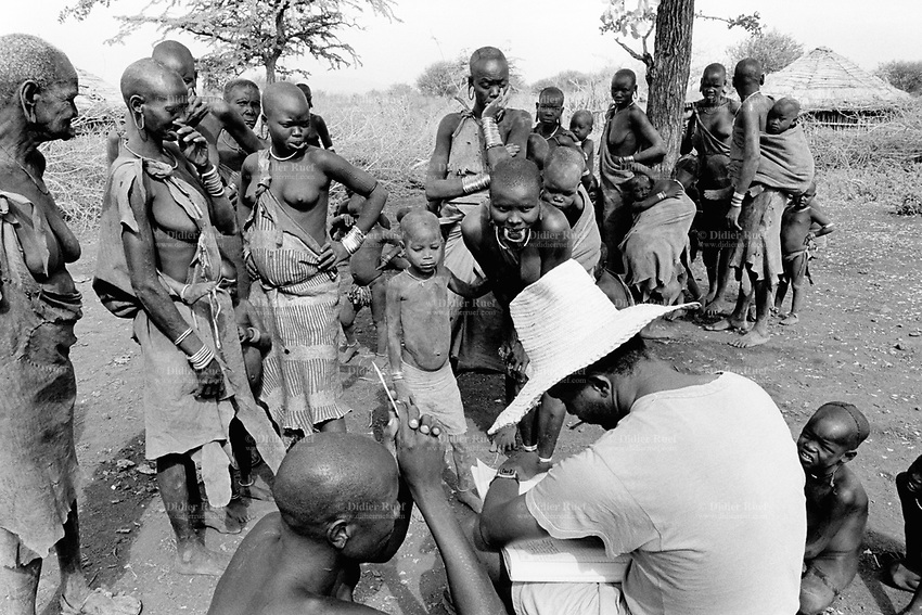 """Ethiopia. South Omo Zone. Salamago district.Hirchu (small village) . Mursi tribe. Mothers waiting for the start by the non-governmental organization (NGO) Médecins Sans Frontières (MSF) Switzerland of the vaccination injections against tetanos, dpt, bcg and measle. MSF Switzerland as part of its health project inoculate children. An ethiopian nurse working for the government and with MSF registers the names of the mothers and their children. The Mursi tribe is an Agro-pastoralist group. Mursi women are known as """"disk-lip"""" women. The bottom lip is slit along its full length and the front bottom row of teeth are pulled out to accomodate the ceramic disk  which is handmade with a rim around which the stretched lip is pulled. The disk is seen as a symbol of beauty and wealth, and often the younger girls will pierce and strech their ear-lobes, inserting a matching disk in the extended lobe. Mursi women' dresses are made out of cow's leather. The Mursi tribe is located in the Debub Omo Zone (South Omo Zone) of the Southern Nations, Nationalities and Peoples's région. © 2001 Didier Ruef"""