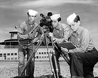 Students at Naval School of Photography working on a practical outdoor assignment, Class 4 (Movies).  Three students using the Eyemo Model Q 35 mm motion picture camera with electric motor drive are all rigged to shoot.  Location: NAS, Pensacola, Florida.  Date: Received, April 13, 1945.  Taken by:  Naval School of Photography.  NARA Ref #: 80-G-311228