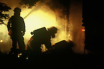 One fire fighter standing, one fire fighter bending over and one fire fighter laying down by the front corner of house
