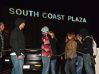 A number of protestors take a break from marching early in the morning on Black Friday (1:07am) while standing in front of the South Coast Plaza sign.  The protesters were tied together by rope, being led by a single protestor dressed in a suit (as a banker), symbolizing how the 1% lead the 99%.
