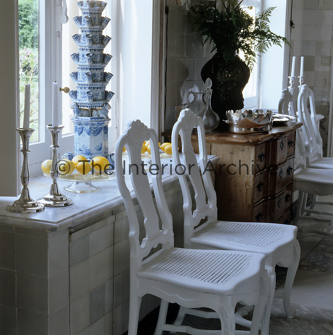 Pairs of white Swedish chairs line this dining room