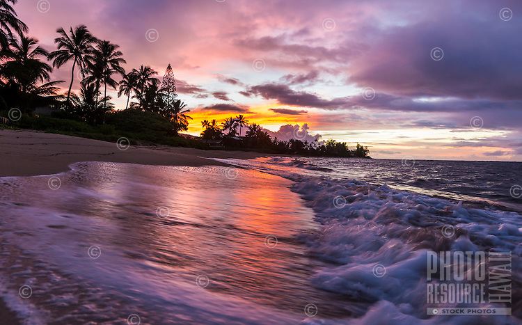 An orange and purple sunset at a beach in Waialua, North Shore, O'ahu.