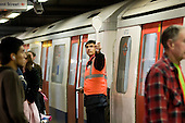 A train guard signals to a driver on the London underground.