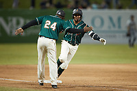 Lolo Sanchez (34) of the Greensboro Grasshoppers slaps hands with third base coach Kieran Mattison (24) after hitting a walk-off 2-run home run against the Hickory Crawdads at First National Bank Field on May 6, 2021 in Greensboro, North Carolina. (Brian Westerholt/Four Seam Images)