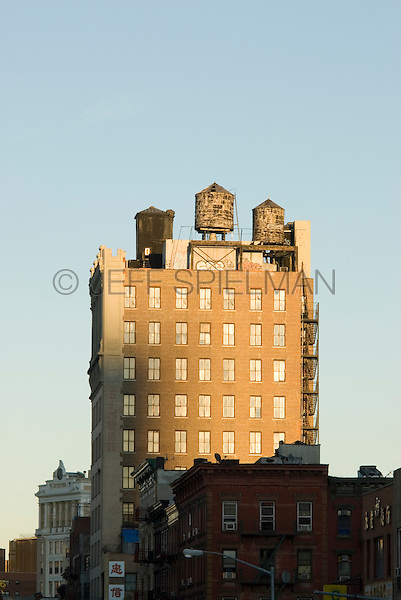 "Iconic Water Towers atop a Classic 1912 Former Bank Building on Manhattan's Lower East Side, Jarmulowsky's Bank Building, 54 Canal Street at Orchard Street, New York City, New York State, USA<br /> <br /> One of the Lower East Side's classic buildings, the Jarmulowsky Bank Builidng was built by architects Rouse & Goldstone in the ""Modern Renaissance Style.""  It was completed in 1912 and was designated a New York City Landmark by the Landmarks Preservation Commission in 2009.<br /> <br /> The bank was established in 1873 by Sender Jarmulowsky, a Russian Jewish immigrant who went on to become one of the Lower East Side's most prominent businessmen....and was also a Talmudic scholar.   He was also one of the Lower East Side's most prominent philanthropists and served as the first president of the Eldridge Street Synagogue. <br /> <br /> Jarmulowsky's Bank was a well known institution among Yiddish speaking Jewish immigrants on the Lower East Side....and their relatives still living in Europe.  Immigrants here in New York City used the bank to send money to their relatives abroad....and to purchase steerage tickets (in Yiddish) so their relatives in Europe could also emigrate to the USA.  World War I broke out two years after this bulding was completed and the bank failed after a bank run as depositers withdrew funds to send to  relatives abroad.  The building was once the tallest building on Manhattan's Lower East Side.<br /> <br /> According to a Yiddish newspaper of the time, Sender Jarmulowsky was "" living proof that in America one can be a rich businessman but also a true, pious Jew.""."