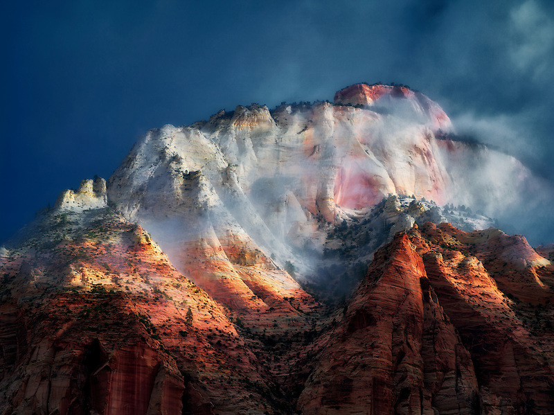 Sun peaking through storm clouds at East Temple. Zion National Park, Utah