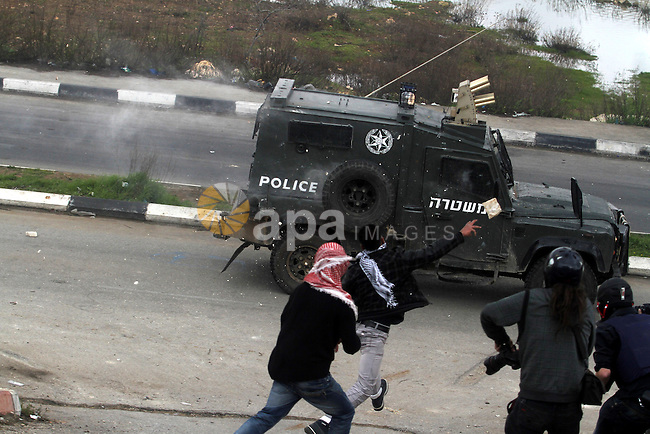 Palestinian protesters throw stones at Israeli soldiers during clashes outside Israel's Ofer military prison following a protest in support of prisoners on hunger strike in Israeli prisons, near Ramallah on February 19, 2013. Some 800 Palestinians serving time in Israeli jails were refusing food in solidarity with four fellow inmates who have been on long-term hunger strike, officials said. Photo by Issam Rimawi