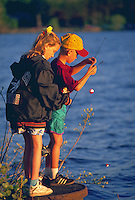 Two children fishing from a dock; boy and girl.