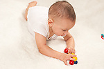 6 month old baby boy on stomach playing with toy using both hands