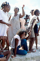 Haiti. Province of Ouest. Port-Au-Prince. Slum of Campêche. Highly densely populated. A voodoo music group is practising his songs and the neighbours (mostly women and girls) enjoy themselves dancing and singing on the music with a strong beat. © 2003 Didier Ruef