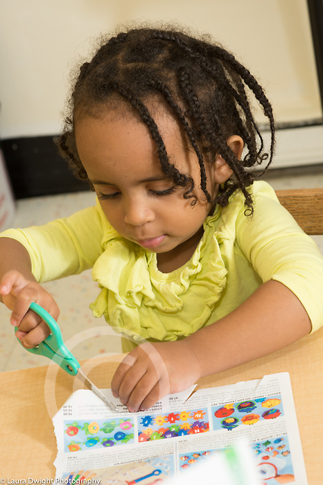 Education Preschool 3-4 year olds girl using scissors to cut catalog page