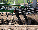 An arena implement works the rodeo arena in preparation for upcoming competition.