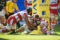 Tomas O'Leary of London Irish forces his way over the line to score despite the efforts of Akapusi Qera of Gloucester Rugbyduring the Aviva Premiership match between London Irish and Gloucester Rugby at the Madejski Stadium on Saturday 8th September 2012 (Photo by Rob Munro)