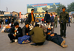 Beijing China 1990s. Unemployed migrant labour force workers wait with their possessions for their trains back to their home towns in the country 1998.