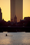 Boston, Massachusetts, skyline, Rower in single racing shell rows the Charles River past Nob Hill at dawn