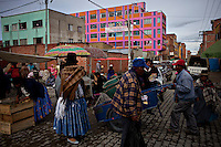 Street fair and local arquitecture.Just 25 years ago it was a small group of houses around La Paz  airport, at an altitude of 12,000 feet. Now El Alto city  has  nearly one million people, surpassing even the capital of Bolivia, and it is the city of Latin America that grew faster .<br /> It is also a paradigmatic city of the troubles  and traumas of the country. There got refugee thousands of miners that lost  their jobs in 90 ´s after the privatization and closure of many mines. The peasants expelled by the lack of land or low prices for their production. Also many who did not want to live in regions where coca  growers and the Army  faced with violence.<br /> In short, anyone who did not have anything at all and was looking for a place to survive ended up in El Alto.<br /> Today is an amazing city. Not only for its size. Also by showing how its inhabitants,the poorest of the poor in one of the poorest countries in Latin America, managed to get into society, to get some economic development, to replace their firs  cardboard houses with  new ones made with bricks ,  to trace its streets,  to raise their clubs, churches and schools for their children.<br /> Better or worse, some have managed to become a sort of middle class, a section of the society that sociologists call  emerging sectors. Many, maybe  most of them, remain for statistics as  poor. But clearly  all of them have the feeling they got  for their children a better life than the one they had to face themselves .