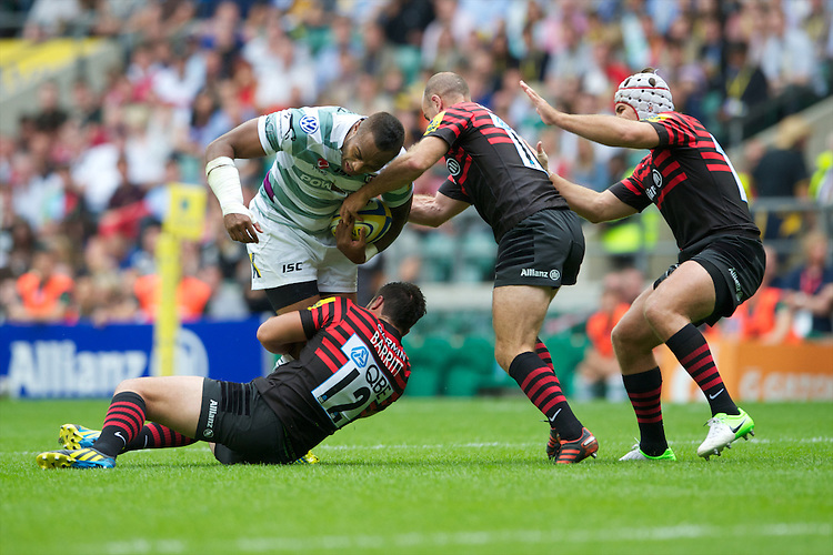 Sailosi Tagicakibau of London Irish is tackled by (L-R) Brad Barritt, Charlie Hodgson and Schalk Brits of Saracens during the Aviva Premiership match between Saracens and London Irish at Twickenham on Saturday 1st September 2012 (Photo by Rob Munro)