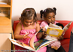 Preschool ages 3-5 two girls sitting on small couch looking at books horizontal