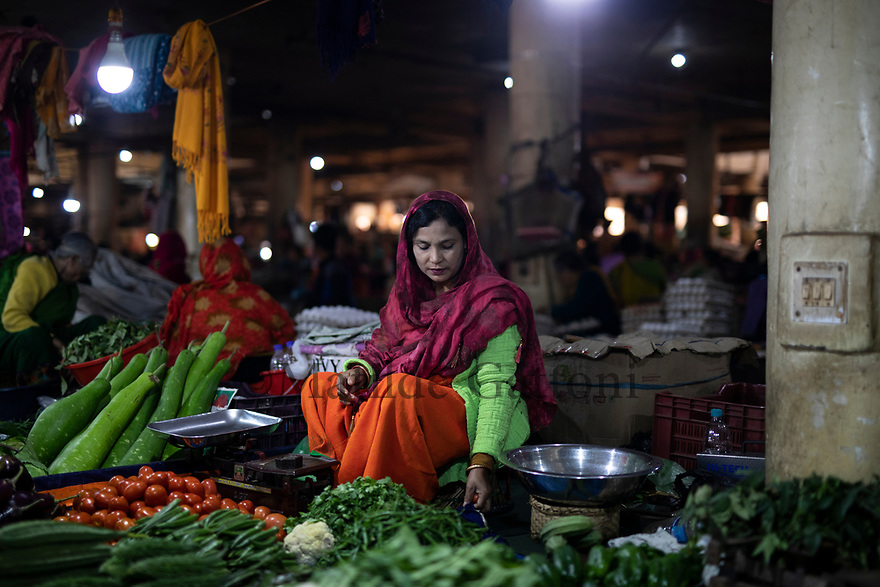 India - Manipur - Imphal - A vegetable seller puts her stall in order during the day. Fresh vegetables are brought every day straight from the countryside to the market.