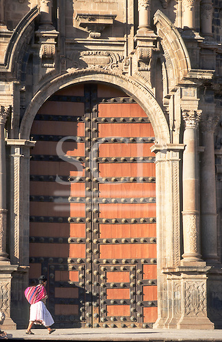 Plaza de Armas, Cusco, Peru. Main door to the cathedral with a woman in traditional dress and bundle walking by.