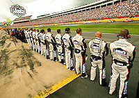 Members of Team Lowe's, the no. 48 Lowe's Chevy Monte Carlo driven by Jimmie Johnson, stand at attention during a moment of silence for veterans, schedules as part of the 2009 Coca-Cola Classic 600 race at the Lowe's Motor Speedway, in Concord, NC. NASCAR Driver David Reutimann won his first Cup race during the rain-shortened event, held May 25, 2009. NASCAR's longest scheduled race went only 227 laps, or 340.5 miles, before officials ended it because of rain. The 2009 race was the 50th running of the Coca-Cola 600. Ryan Newman and Robby Gordon finished second and third respectively.