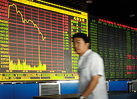 Chinese investor in a stock exchange of Beijing. Chinese share prices broke through the psychologically important 4000-mark for the first time ever last week and dealers said the sustained Chinese advance is being driven by massive inflows of fresh funds as smaller investors take their money out of low-return bank deposits and punt on stocks..15 May 2007