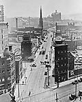 Pittsburgh PA: View of Duquesne University from the corner of Grant Street and Sixth Avenue.  During this time, it was common for Brady Stewart to get on a roof of an office building and take photographs.  Company signs on city buildings include:  Venus Pencils, American Bank, M. Berardini's Bank, National Fireproof Company,  Waverly Printing Company, and Kuppenheimer Clothes at Kaufmann's Store