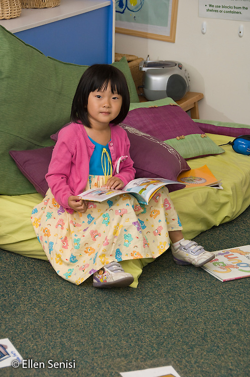 MR / College Park, Maryland.Center for Young Children, laboratory school within the College of Education at the University of Maryland. Full day developmental program of early childhood education for children of faculty, staff, and students at the university..Portrait of student (girl, 5,Asian American) sitting on pillows in classroom and reading..MR: Liu1.© Ellen B. Senisi