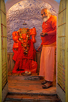 India, Dehradun.  Hanuman, a Hindu Deity in the   Tapkeshwar Hindu Temple with Hindu Priest.  Note monetary donations at the base of the statue.