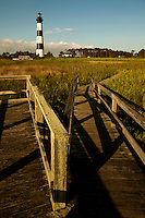 A wooden boardwalk path leads through the marsh grasses to the stately Bodie Island Lighthouse located on Bodie Island on North Carolina's Outer Banks. The light house, built in 1872, stands 156 feet tall and is located on the Roanoke Sound side of the first island that is part of the Cape Hatteras National Seashore. The lighthouse is just south of Nag's Head, a few miles before Oregon Inlet. The conical-shaped lighthouse has white and black bands with a black lantern house. Charlotte NC photographer Patrick Schneider has extensive photo collections of the following lighthouses: Bodie Island Lighthouse, Bald Head Island Lighthouse, Cape Fear Lighthouse, Cape Hatteras Lighthouse, Cape Lookout Lighthouse, Currituck Beach Lighthouse, Diamond Shoal Lighthouse, Federal Point Lighthouse, Oak Island Lighthouse, and Ocracoke Lighthouse on Ocracoke Island.