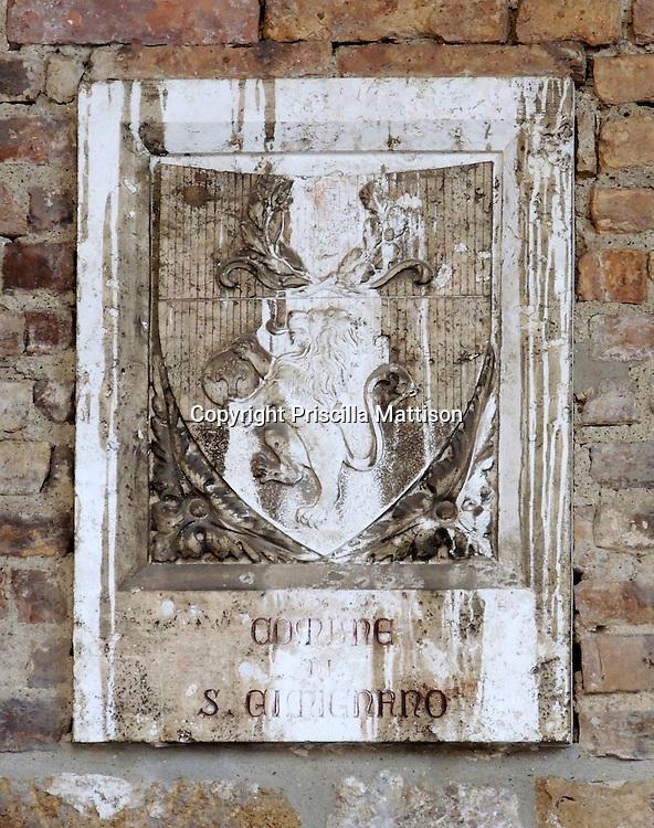 San Gimignano, Italy - October 4, 2012:  A stone plaque is set into a brick wall.