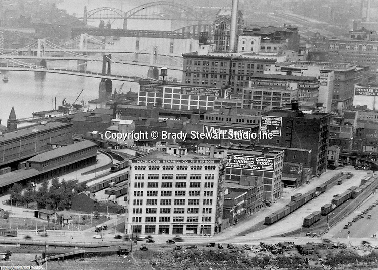 Pittsburgh PA:  View of the Point Buildings and railroad yards and the new 7th & 9th Street bridges;  self-anchored suspension bridges spanning the Allegheny River.  Company signs are the city buildings include:  Victor Radio, Demmler & Schenck, Mackintosh Hemphill Company, Daugherty Company Canned Foods, Imperial Power Building, Union Electric Company, & General Electric Wiring Systems