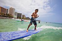 Young boy surfing in Waikiki on a long board
