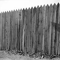 Parking sign along wood fence<br />