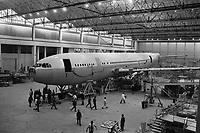 Usine de l'Aérospatiale de Saint-Martin-du-Touch, grand hall de montage. 5 février 1972. Vue d'ensemble de l'Airbus A300 B (vue de côté, partie avant de l'avion), cales en bois sous l'avion, échaffaudages ; techniciens autour de l'avion. Cliché pris lors du 1er déplacement tracté de l'avion encore en cours de montage.