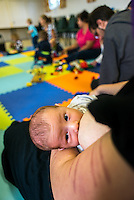 """Close-up of breastfeeding a newly arrived baby at a singing and signing group.Image from the breastfeeding collection of the """"We Do It In Public"""" documentary photography picture library project: <br />  www.breastfeedinginpublic.co.uk<br /> <br /> <br /> Berkshire, England, UK<br /> 27/09/2013<br /> <br /> © Paul Carter / wdiip.co.uk"""