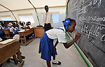 A girl does math on a chalkboard during class at the Notre Dame de Petits school in Port-au-Prince, Haiti. The school's building collapsed in the January 2010 earthquake, and while some classes are conducted in the ruins, other classes meet in large tents provided by International Orthodox Christian Charities.