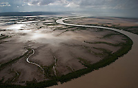 Aerial of mud flats just outside town of Wyndham.  This scene is about one minute away from the landing strip at Wyndham. We circled in front of this single cell storm as it moved across the landscape.  Contact for this is our pilot: Oasis Air Pilot--Ryan 0409209478..Aerials are mostly the King River, but it is hard for me to be sure because there are so many snaking rivers/creeks through these mudflats.  These mudflats are drivable during the dry season.  This is mpossible to do during the wet... The rains wash the dirt into the rivers and creeks and the silt runs out to the ocean.  There is so much silt that the pearl divers I photographed can't even see their hands in front of their faces during this period..