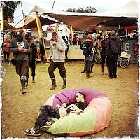 """Fusion-Festival 2014 auf dem Gelaende des Kulturkosmos e.V. in Laerz/Mecklenburg-Vorpommern.<br /> Bis zu 65.000 Menschen kommen jaehrlich fuer 5-6 Tage  zur """"Fusion"""" nach Laerz.<br /> Das linke Festival, was von den Besuchern und Machern scherzhaft auch als """"Ferienkommunismus"""" bezeichnet wird, ist eine Mischung aus Techno-Dancefloors, Theater und Live-Auftritten von politischen Bands.<br /> Die Karten fuer dieses Festival sind nur ueber die Fusion-Internetseite per Losverfahren zu kaufen. Nur ca. jede dritte bis vierte Anmeldung fuer eine Karte hat Erfolg.<br /> Im Bild: Am dritten Festival-Tag kann mancher vor Erschoepfung nicht mehr.<br /> 29.6.2014, Laerz<br /> Copyright: Christian-Ditsch.de<br /> [Inhaltsveraendernde Manipulation des Fotos nur nach ausdruecklicher Genehmigung des Fotografen. Vereinbarungen ueber Abtretung von Persoenlichkeitsrechten/Model Release der abgebildeten Person/Personen liegen nicht vor. NO MODEL RELEASE! Don't publish without copyright Christian-Ditsch.de, Veroeffentlichung nur mit Fotografennennung, sowie gegen Honorar, MwSt. und Beleg. Konto: I N G - D i B a, IBAN DE58500105175400192269, BIC INGDDEFFXXX, Kontakt: post@christian-ditsch.de<br /> Urhebervermerk wird gemaess Paragraph 13 UHG verlangt.]"""