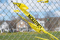 Caution tape is seen on a fence with residential houses in the background during the ongoing Coronavirus (COVID-19) global pandemic in Belmont, Massachusetts, on Fri., April 17, 2020. The fence surrounds Belmont's Town Field, one of the many parks and playgrounds closed to the public for the duration of the pandemic as a way to enforce social distancing protocols.