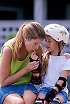 mother comforting, kissing bleeding index finger of little girl who fell while rollerblading
