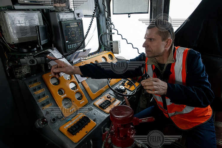 Engineer Alexander Mironovich operates a radio in the driver's cab of a locomotive on the Obskaya-Bovanenkovo railway that links the Gasprom Bovanenkovo gas field to the outside world.