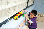 Education preschool 3-4 year olds boy playing by himself pushing vehicles along window sill talking to himself