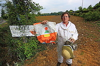 France, in Bretagne, the apiary of Loic Leray, a professional beekeeper.He hold a bag of seeds with systemic pesticides.///France, en Bretagne, le rucher de Loïc Leray un apiculteur professionnel.