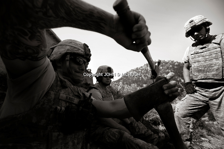 US Staff Sergeant Kirby from Charlie Company, 1/503rd (Airborne), 173rd Brigade, repairs an axe while his squad uses axes and handsaws to clear trees outside Speray Combat Outpost in Khowst province, Afghanistan, 7 May 2008. (John D McHugh)