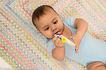 Infant boy age 6 months on back holding toy, ring with pieces that move when shaken