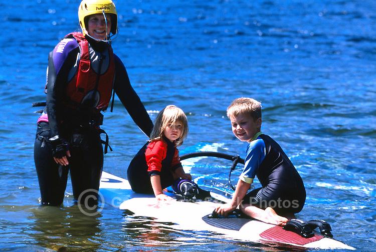 Woman windsurfing with Family on Nimpkish Lake, Vancouver Island, BC, British Columbia, Canada