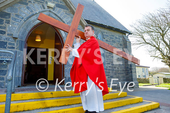 Fr Francis Nolan carrying the cross on Good Friday to the Church of the Purification in Churchill.