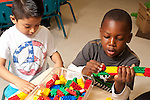 Education Preschool 3-4 year olds two boys playing with colorful plastic connecting building bricks side by side