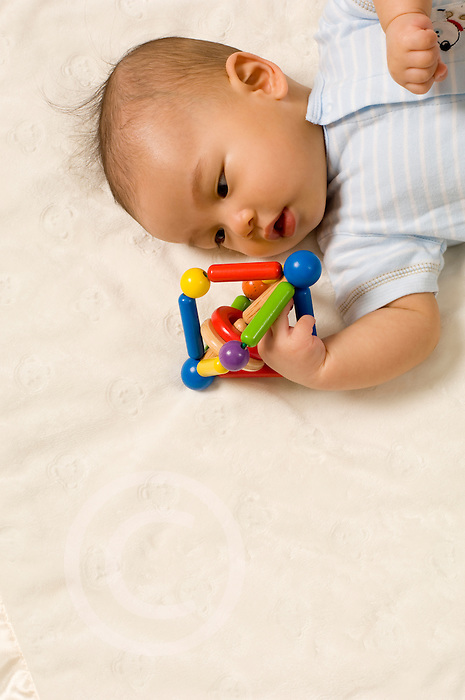 4 month old baby boy Chinese American on back closeup grabbing toy
